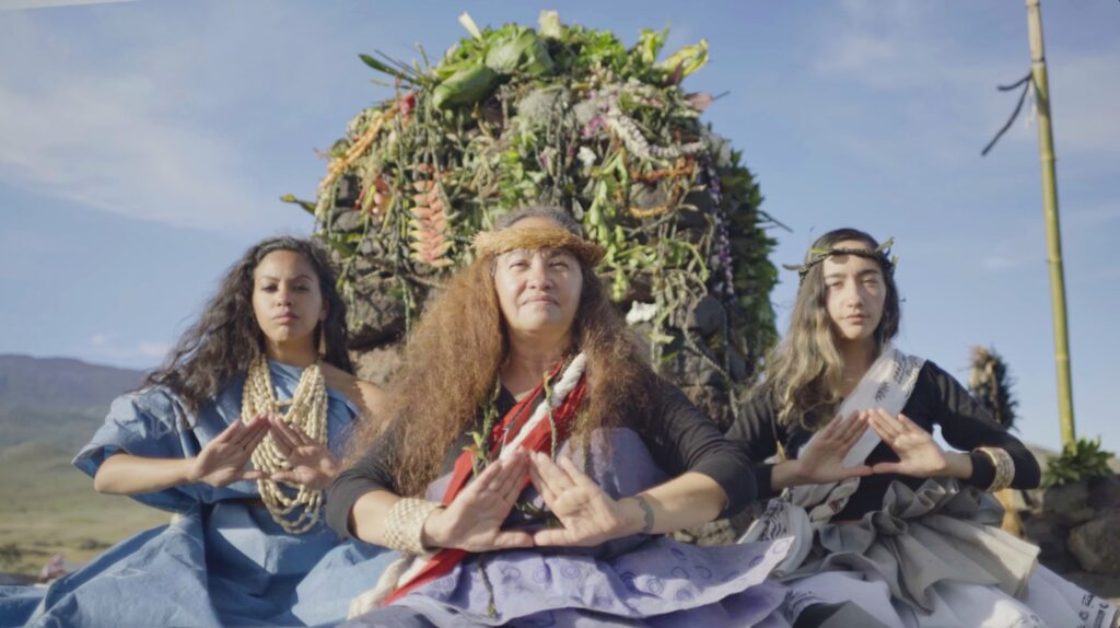Three women in traditional Hawaiian clothing sit at the base of mount Mauna Kea.