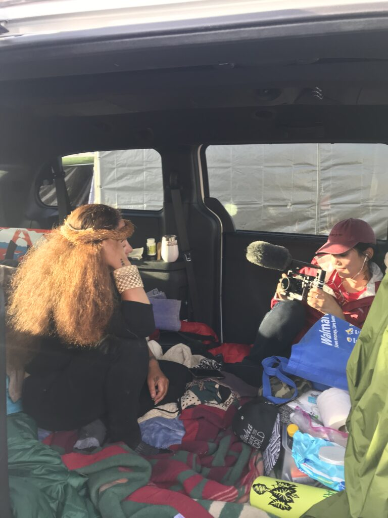 Two women sit in a van, illuminated by golden sunlight. One woman is pointing a camera and filming the other woman.