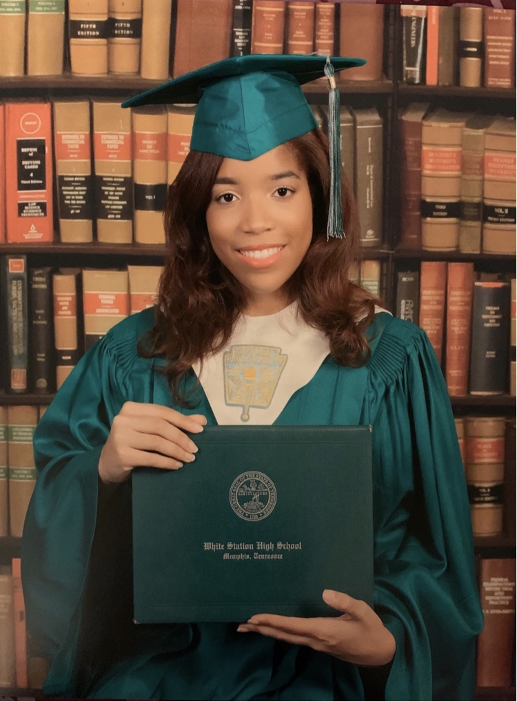 Author Maya Ashe stands wearing a green graduation cap and gown and holds her diploma with National Honors Society recognition.